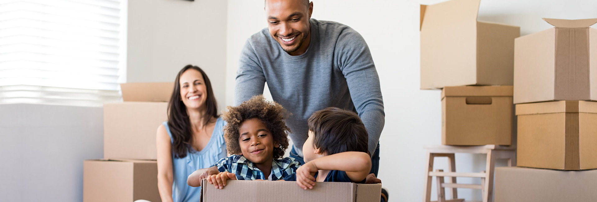 family happily playing on box